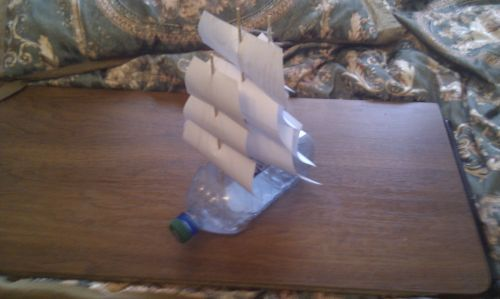 make a sailboat from an old plastic bottle, some wooden sticks and paper