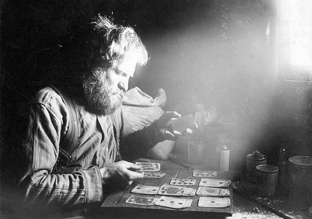 Charles Ainsworth playing cards inside cabin at 60 Above on Sulphur Creek, Yukon Territory by UW Digital Collections on Flickr.