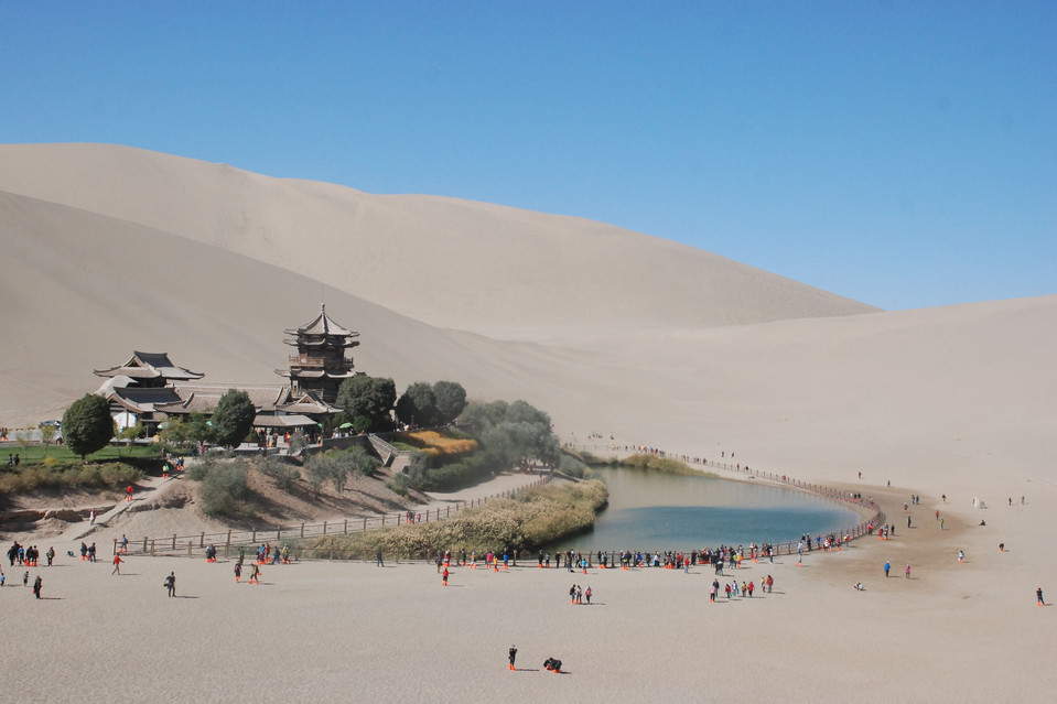 inothernews:  FERTILE SCAR  Tourists visited Crescent Lake in Dunhuang, Gansu province, China, Thursday. Dunhuang was a major stop along the ancient Silk Road.  (Photo: Zhang Xiaoliang / Xinhua / Zuma Press via The Wall Street Journal)