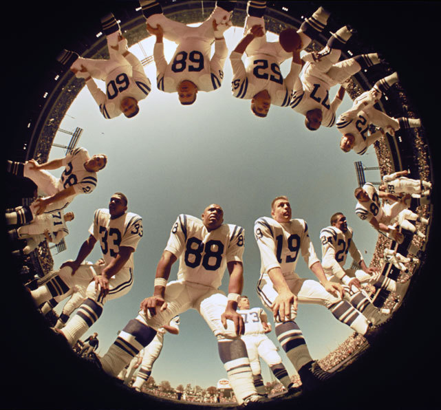 A fisheye ground view of John Mackey (88), Johnny Unitas (19) and the rest of the Baltimore Colts huddle up during practice at Memorial Stadium. (Neil Leifer/SI) SI VAULT: No Unitas, no worries for the Colts (10.21.68)