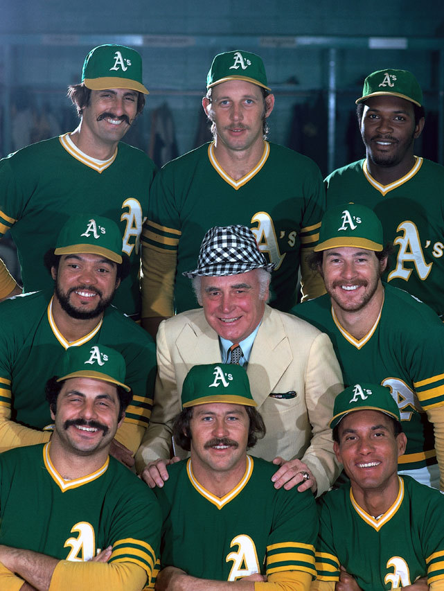 Athletics owner Charlie Finley poses with players (clockwise from top left) Rollie Fingers (34), Joe Rudi (26), Vida Blue (14), Gene Tenace (18), Bert Campaneris (19), Jim Catfish Hunter (27), Sal Bando (6), and Reggie Jackson (9) during a 1974 SI photo shoot. The team would win the World Series a couple months later. Can this year's squad bring another championship to Oakland? (Neil Leifer/SI) VERDUCCI: Oakland reminds us of why we love baseballSI VAULT: Catfish Hunter leads A's into playoffs (10.7.74)