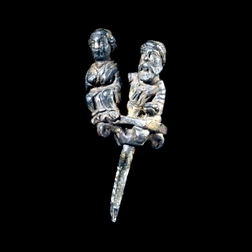 ancientpeoples:  Silver Pin Parthian, 2nd century ADSaid to be from Masjid i-Suleiman, south-west Iran This silver pin head is decorated with an extremely detailed representation of a Parthian couple at a banquet. It is said to have been found at Masjid-i Suleiman but, unlike some bronze objects from the site which seem to have served as votive objects, this silver piece may have had a funerary purpose. It may therefore have come not from the Parthian period sanctuaries at the site but from somewhere - perhaps a grave - in the surrounding region. The couple seem to be shown at a funerary banquet, examples of which are well known from the reliefs of Palmyra, particularly in the second and third centuries AD. The gesture of putting a comforting hand on the partner or spouse, common in Roman art, is also known from contemporary Palmyrene reliefs. Both the male and the female figure have a similar hairstyle with long hair ending in rolls. This style was fashionable at the end of the second century AD. (Source: The British Museum)