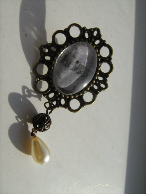 Brass brooch frame with metal pin back, brass filigree bead, and glass pearl drop: Elizabethan etching reproduction image and glass cabochon.Wear a little piece of Shakespeare's London with this Tudor-style brooch and fragmentary glimpse of London Bridge as it used to be! Couples up beautifully with a quilted jacket, or on a blazer, but don't limit yourself! The key to great style is not being afraid to experiment.