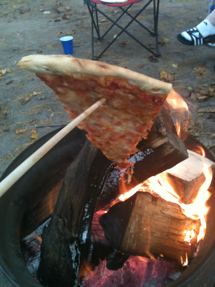 i went camping over the weekend and this is me roasting pizza over an open fire
