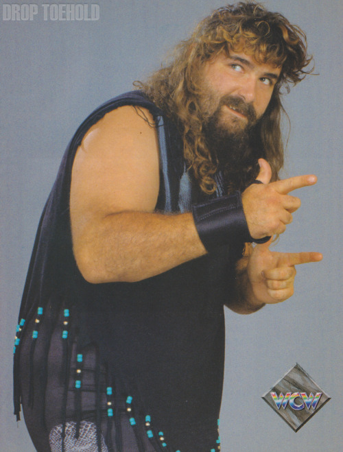 "Cactus Jack - WCW Magazine Collector Series Special #3 [December 1992]  ""'This is gonna hurt you more than it's gonna hurt me! Bang, bang!' Cactus jack's countenance is definitely frightening, but that may be the least frightening thing about this wildman from Truth or Consequences, New Mexico! When Jack steps into the ring, things thought to be impossible and unlikely suddenly seem possible and inevitable: flying ellbow-smashes from the ring apron to the arena floor, suplexes on concrete and clothelines that send both competitors hurtling over the ropes! Recklessness is the hallmark of this 6'4"", 297-pounder, but don't for a minute think that equates with carelessness. There is a method to Jack's madness, as evidenced by his ability to have remained at or near the top of the WCW ratings for over a year, and his unpredictability affords him a significant psychological advantage over anybody who happens to be courageous enough to step into the ring with him.""  It's almost comforting to see exactly how little Mama Foley's Baby Boy has changed over the years. Bang, bang!!"