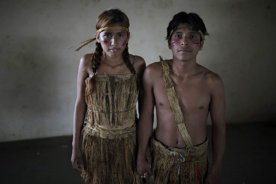 Erika Kanacmi, left, and Denis Capi, an Esse Ejja indigenous couple, posed for a picture before a mass wedding ceremony in Cobija, Bolivia, Saturday. The government organized the 'Collective Marriage From our Identity 2012' ceremony. Juan Karita/Associated Press