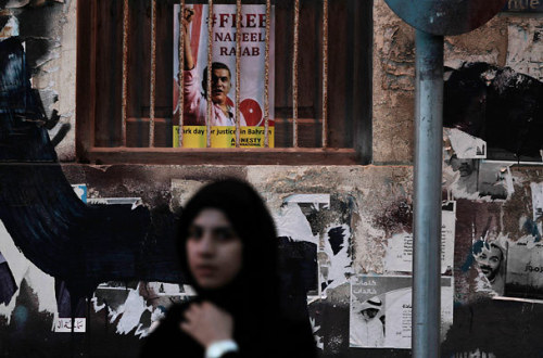 fotojournalismus:  A Bahraini woman walks past a poster demanding the freedom of jailed human rights activist Nabeel Rajab during the third day mourning procession of Rajab's elderly mother, Rabab, in Manama, Bahrain, Sunday, Oct. 7, 2012. Rajab is on a hunger strike after authorities, who allowed him to leave prison for the first day of funeral rites for his mother, revoked his permission to participate in the following two days of rites, according to relatives and human rights activists. [Credit : Hasan Jamali/AP]