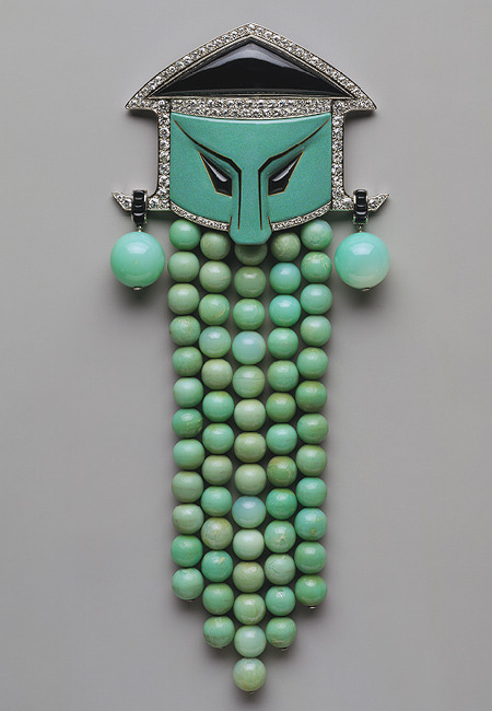 Dress ornament, ca. 1923Georges Fouquet (French, 1862–1957)Jade, onyx, diamonds, enamel, platinum H. 8 7/8 in. (22.5 cm), W. 3 3/4 in. (9.5 cm)Gift of Eva and Michael Chow, 2001 (2001.723) @credits  In 1895, Georges Fouquet took over the Paris jewelry firm—at the time known for its wide range of historicist styles—established by his father in 1860. Reinvigorating it with a decidedly modern spirit, he continued to supply his fashionable clientele with exquisite jewels in the latest styles until the late 1930s. This dress ornament typifies theatrical taste of the mid-1920s for the exoticism of the Far East. Its unexpected combination of colors and juxtaposition of materials—which include Asian jade—are appropriately matched to the motif of a Chinese mask. The extraordinarily large scale of the jewel suggests that it was intended to be a tour-de-force exhibition piece; its weight would easily have torn or compromised the drape of a delicate dress fabric.