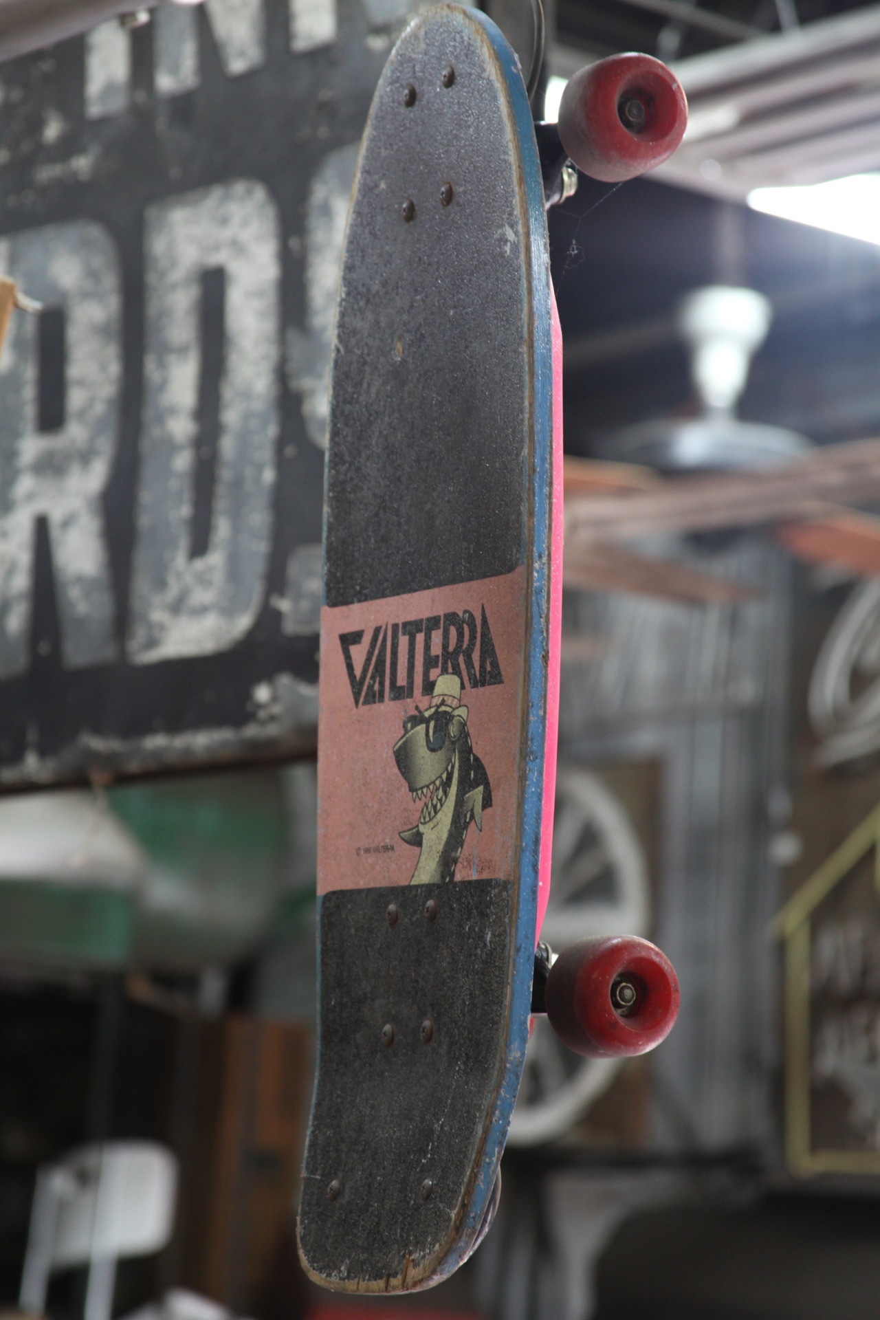 Old Valterra skateboard hanging up in a junk yard.