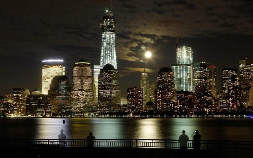 The moon rises behind the skyline of New York's Lower Manhattan and One World Trade Center as people stand along the Hudson River in Jersey City, New Jersey. Picture taken with a 30-second exposure. (Picture: REUTERS/Gary Hershorn)