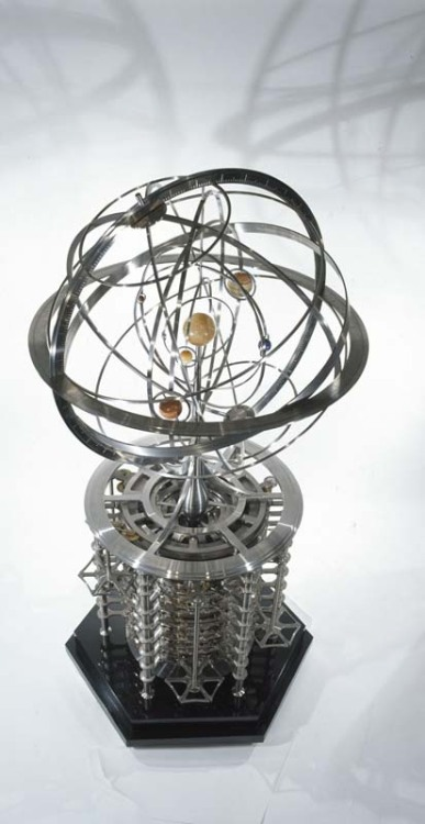 "Above: The most complex orrery of the collection showing a star system with multiple solar planes Item #: SCP-341 Object Class: Safe Special Containment Procedures: The exhibition hall of Reliquary Research and Containment Site-76 has SCP-341 on display for all Research and Command personnel to view. Description: A collection of eleven brass and iron orreries found in a large storage room of a basement at Oxford comprise SCP-341. Each orrery is a rough scale model of a different extra-solar star system, complete with planets, moons and one or more suns in the center. A unique clockwork mechanism under each orrery allows the brass models of planets and moons to spin on axis and rotate around each model of its parent star(s). Testing dates each machine to between 150-200 years old, but without any specific markings, researchers have been unable to determine who created them. A design found with the collection that either was never constructed or is simply missing. The orrery collection of SCP-341 were almost released into the hands of a local museum when an SCP astronomer with a piqued interest in the discovery recognized one of the orreries (SCP-341E) as star system Upsilon Andromedae-A (unique for being a ""Solar Twin"" of our own sun with ""Hot Jupiter"" like planets). Further research has matched five of the eleven orreries with possible known extra-solar systems. Including: Beta Canum Venaticorum 37 Geminorum HD 98618 18 Scorpii One orrery, known as ""the wheel of doom"" amongst researchers, depicts a similar solar system very reminiscent of our own Sol's. Though the planets and Sun themselves are neither near to scale nor spaced proportionately, the presence of seven major planets of our own system are fairly obvious, including Saturn and its rings and the tilted side of Uranus. There are also 5 minor planets included beyond the orbit of Neptune. The orrery is missing a model of Earth and instead has a free Moon roaming through a debris field similar to the asteroid belt present between Mars and Jupiter. From top: A possible model of Beta Canum Venaticorum, displaying several yet to be confirmed inner planets; an accurate model of the system HD 98618; a simple model depicting a binary star system of an undiscovered location"