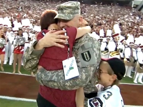 Military dad surprises kids, wife at football game (Photo: NBC News) Army Sergeant First Class Scott Faile surprised his wife Tammy and two of their kids this past weekend at the South Carolina-Georgia college football game by walking out on the field for an emotional reunion that's become a viral sensation online.  Watch the video here.