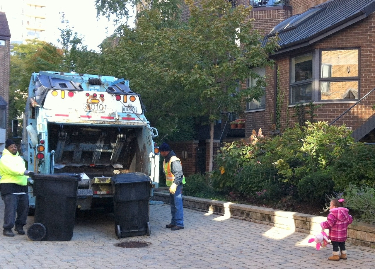 "Garbage day normally falls on a Tuesday, but because of Columbus Day, it was pushed back to Wednesday this week…. Meaning Hazel has been on ""Garbage Truck Watch"" for the past 24 hours.Looking out the window every few minutes with her eyes growing wide each time an engine rumbled down Clark Street. Yup. Garbage Trucks are my daughter's newest obsession.Buses & Garbage Trucks(Where does she come up with this stuff?)This morning, while playing in her room, we heard the unmistakable beeps of an approaching garbage truck.  And I had an idea…  One of those ideas that never in a million years would have registered as a good idea before becoming the mother to a toddler with this affinity for oversized vehicles Hazel…want to chase the Garbage truck?! Based on her reaction, you would have thought my girl had just won a lifetime supply of licorice or a trip to Disney World!  She literally put her hands to her cheeks and screamed. Hurriedly, we grabbed our boots & her best friend piglet and went bounding down the stairs Christmas-Morning-Style to see the Trash-Eater up close! Once outside, Hazel waved enthusiastically to the garbage men and said ""Good Job"" to the truck each time its automated arm lifted/dumped one of the trash bins into the compactor. We followed (a safe distance) behind the action for the entire length of our block.  20 minutes or so.The novelty did not wear off.  Before pulling away, the driver told Hazel - ""we'll see you next week""And she replied: OK. I guess we now have a standing weekly date with the sanitation team. Simple pleasures, my friends."