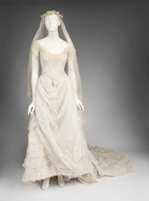 Julien's Auctions:  An Emmy Rossum wedding dress worn for her role as Christine in the film The  Phantom  of  the  Opera  (Warner Bros., 2004). The gown consists of a white lace trimmed bustier bodice and floor-length skirt and ruffled petticoat. With long veil and pearl trimmed headpiece.
