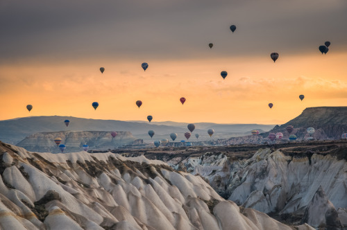 """Flying hot air ballons in Turkey"" by Natapong P. Hot-air balloons journey over the landscape of Cappadocia, Turkey"