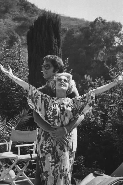 (1965) Actress Lana Turner, 49, w. arms outstretched as she is gently embraced fr. behind by her seventh husband Ronald Dante, a 49-yr-old nightclub hypnotist, on the patio of their hilltop home.   About 6 monthes into the marriage Dante (aka Dr. Dante aka Ronald Pellar ) abandoned Turner after she loaned him $35,000 for a business venture.