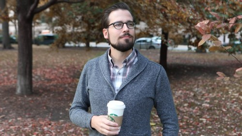 The Onion: Mr. Autumn Man Walking Down Street With Cup Of Coffee, Wearing Sweater Over Plaid Collared Shirt