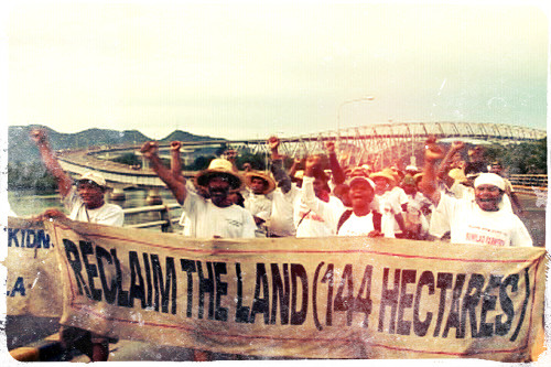 "ellobofilipino:  The Sumilao Farmers crossing the San Juanico Bridge. November 2, 2007. To chants of ""Samar na gyud!"" the farmers crossed to Santa Rita, Samar from Tacloban City. Starting from San Vicente, Sumilao, Bukidnon on October 10, 2007, the farmers would reach Manila by foot and barge on December 3, 2007. The march of the Sumilao Farmers was launched also on the 10th anniversary of a hunger strike they launched in 1997 to protect their claims against business interests encroaching on their land. The protest was resolved in a controversial settlement which placed the farmers at a disadvantage. The farmers would eventually retake their land in March 2008, after more than a decade of struggling against a huge business conglomerate, several public officials and private individuals who were interested in their land. But the victory was bittersweet. Just three months after they reclaimed their land, one of their leaders, paralegal Rene Peñas (leftmost in the picture above), would be murdered by hired assassins as he was on his way home from a meeting. The case remains unresolved."