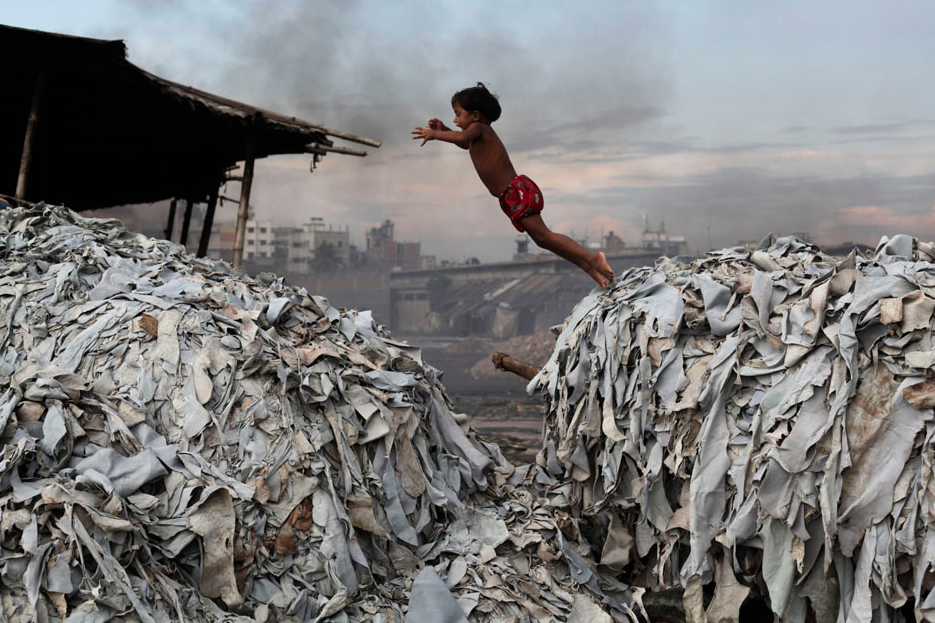 A child jumps on the waste products that are used to make poultry feed as she plays in a tannery at Hazaribagh in Dhaka, Bangladesh, October 9, 2012. Luxury leather goods sold across the world are produced in a slum area of Bangladesh's capital where workers, including children, are exposed to hazardous chemicals and often injured in horrific accidents, according to a study released on Tuesday. None of the tanneries packed cheek by jowl into Dhaka's Hazaribagh neighborhood treat their waste water, which contains animal flesh, sulfuric acid, chromium and lead, leaving it to spew into open gutters and eventually the city's main river. REUTERS/Andrew Biraj