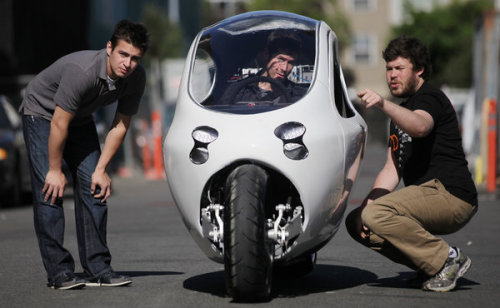 "Are Enclosed, Stabilized Electric Motorcycles The Vehicles of the Future?  For Some Drivers, an Electric Motorcycle Could Be the Best of Both Worlds- Brian X Chen via NY Times Zipping around on a motorcycle can be fun, but being in a downpour or an accident on one is not. Driving a car is safer and more comfortable, but traffic and parking can be annoying. What if you got rid of the bad parts of both? You might end up with something like the C-1, an electric motorcycle that looks as if it came out of the movie ""Tron."" For protection, the bike is encased in a metal shell, and it is controlled like a car, with a steering wheel and foot pedals. Two big gyroscopes under the floor are designed to keep it from tipping over, even when a car hits it from the side. The C-1's top speed is 120 miles an hour, and it can travel 200 miles on a full charge.  via wildcat2030, ht stoweboyd FWIW, I might be willing to try one of these if it had 3 wheels instead of 2. Related articles Students designing an omnidirectional sphere-wheeled electric motorcycle (gizmag.com) Carbon-Fibered Electric Motorcycle to Be Tesla of Electric Motorcycles? (bfreenews.com) The Fastest Electric Motorcycle Is Also the Most Practical (wired.com) 2013 Zero Motorcycles Lineup Has More Range, Twice The Power (gas2.org)"