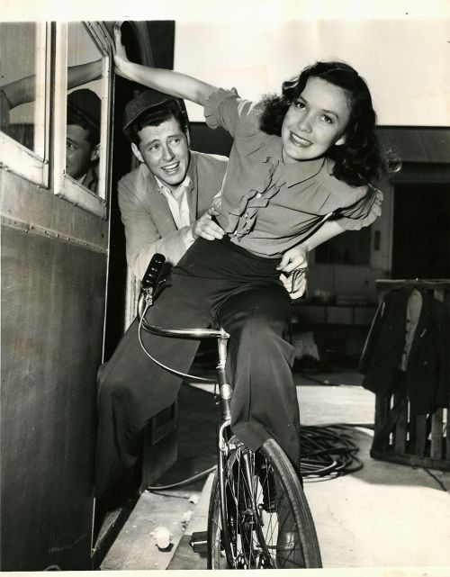 Mary Anderson and Edward Ryan ride a bike. Awkwardly.