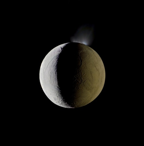 timelightbox:  Enceladus vents water into space from its south polar region. The moon is lit by the Sun on the left, and backlit by the vast reflecting surface of its parent planet to the right. Icy crystals from these plumes are likely the source of Saturn's nebulous E ring, within which Enceladus orbits. (photo:NASA / JPL-Caltech/Michael Benson/Kinetikon Pictures) Multimedia artist Michael Benson begins with filtered, black-and-white imagery sent back by space probes at the edge of existence. He ends with colorful, high-definition visions of a universe in motion. See more images and watch the video here.