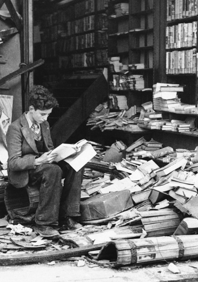 A boy sits reading in a bombed bookstore, London, 1940.