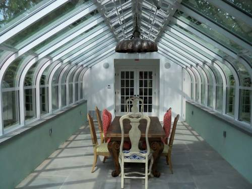 A conservatory can create an intimate dining space. Tables, chairs, and a chandelier can be used for warming the space to entertain friends and family.