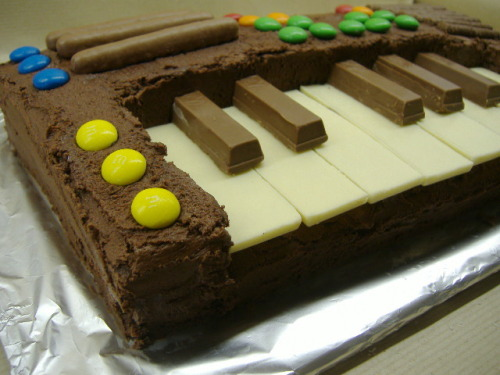 katachi-kazami:  kittykichi:  cardboardlife:  Keyboard cake. The black keys are Kit Kat pieces and the white keys are small Milkybars turned upside down so the smooth side is on top. The rest of the cake is just two rectangular chocolate sponge cakes. I cut a smaller rectangle out of one of the cakes to make space for the keys, sandwiched them together with chocolate buttercream, covered the whole thing with more buttercream and decorated it with M&M's and chocolate fingers.  ;3;  I think I found a cake for my birthday~ :3