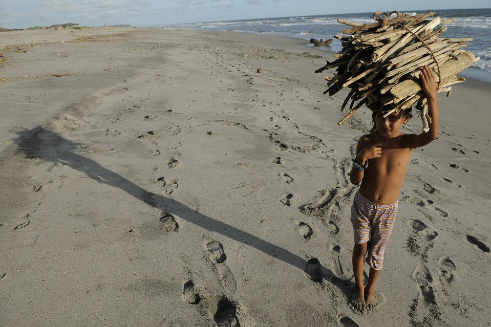 A girl carried wood for her family on Costa del Sol beach, near San Salvador, El Salvador, Thursday. The United Nations proclaimed the day the International Day of the Girl Child, to recognize girls' rights and the unique challenges girls face around the world. Luis Galdamez/European Pressphoto Agency