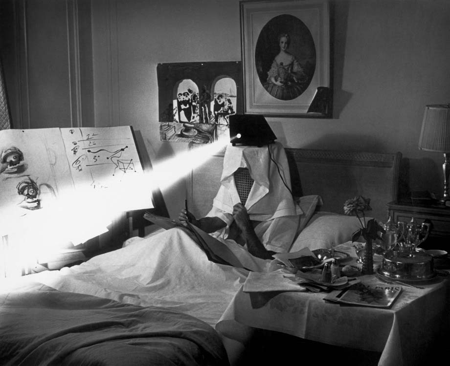"workspaces:  Salvador Dalí in bed in 1964, projecting pieces of dirty paper ""to stimulate his inspiration."" 