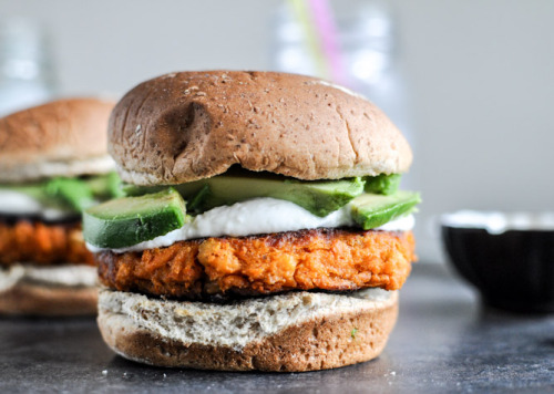 Smoky Sweet Potato Burgers with Roasted Garlic Cream and Avocado  YIELD: 4 BURGERS   PREP TIME: 45 MINUTES   COOK TIME: 10 MINUTES   TOTAL TIME: 55 MINUTES   ingredients:  2 cups coarsely mashed sweet potatoes (or yams), about 2 large potatoes2 bulbs of roasted garlic1 cup cannellini benas (rinsed and drained if canned)2 garlic cloves, minced1/3 cup panko bread crumbs1/3 cup oat flour (or all-purpose, wheat, etc)1 large egg, lightly beaten1 1/2 teaspoons smoked paprika1 teaspoon onion powder1 teaspoon salt1/2 teaspoon pepper1/8 teaspoon cumin2-3 tablespoons olive oil1 avocado, sliced2/3 cup plain greek yogurt or sour cream1 teaspoon maple syrupextra salt and pepper for seasoning yogurt/cream 4 whole wheat buns    directions:  To roast garlic, see this tutorial. I like to roast a few bulbs at once (like 4-5) to have for the week. Pierce potatoes (I used 2 large) all over with a fork and place on a paper towel, setting in the microwave. Microwave for 5 minutes, then flip and cook for 5 minutes more. Remove, slice in half and let cool until you can scoop out the flesh. In a large bowl, coarsely mash beans with a fork. Add in sweet potato and mash together, then add in spices, salt and pepper, minced garlic, egg, panko and flour. Mix together until combined, then place bowl in the fridge for 15-20 minutes. This helps form them into patties, but as a warning they are still somewhat messy. While mixture is chilling, combine yogurt/sour cream with 2 bulbs (squeezed out) of roasted garlic cloves, maple syrup and a sprinkle of salt and pepper in a blender or food processor. Process until smooth then set aside until ready to use. Heat a large skillet over medium heat and add 2 tablespoons olive oil. Remove mixture from fridge and form into 4 equal patties, then place in the skillet once hot. Since the mixture can be wet and messy, do not move until they are fully cooked and golden on one side! This takes about 5-6 minutes. Then, add more oil if needed (this really helps cook them) and flip burgers very gently. Cook for another 5-6 minutes. Toast buns if desired.