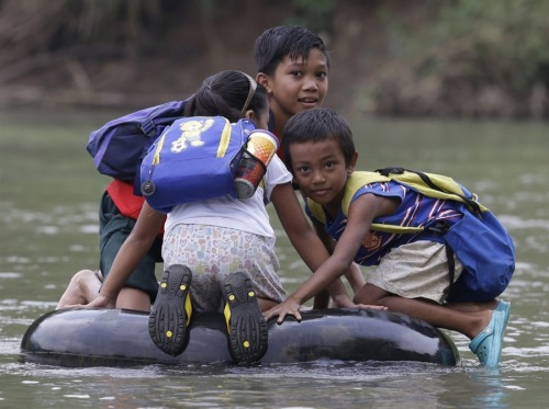 fotojournalismus:  School children use an inflated tire tube to cross a river to go to a public school in Rizal province east of Manila, Philippines, on Oct. 12, 2012. Access to education is a problem in the Philippines, especially in rural areas, but enrollment rates remain relatively high. According to UNICEF, 85% of Filipino children are enrolled in elementary school, though only 62 percent finish high school. [Credit : Bullit Marquez / AP]
