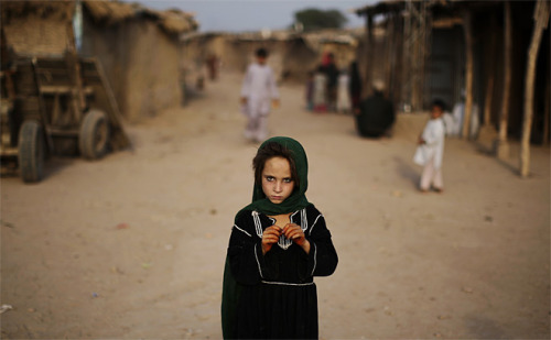 fotojournalismus:  Afghan refugee Naseema Zurab, 7, stands in a slum on the outskirts of Islamabad, Pakistan, Friday, Oct. 12, 2012. [Credit : Muhammed Muheisen/AP]