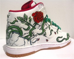 Mirror Mirror Custom Nike Dunks by Jason Bryant @BryantPaintings Vines twirling around the shoes onto the wall and rose petals going to the ground as they fall. As part of a transition from regular canvas artist Jason Bryant added painting skate decks to his arsenal. Looking to use another unconventional canvas Bryant decided to use a high top Nike Dunk which was a natural choice considering the his long interest in Nike and skateboarding since the 1980s. The pair titled Mirror Mirror is part of his full exhibition Smoke and Mirrors at the Porter Contemporary Art Gallery in New York that explores moments of human weakness and deception in photo-realistic oil paintings of vintage film still shots combined with vintage skateboard inspired graphics.  Specifically for these Mirror Mirror Nike Dunks Bryant first primed the entire upper white prepping for a mirrored design on each shoe. The first graphics made were a hand painted image of 1940s and 50s actress June Allyson looking into her reflection, though with some obstruction. In the way of her view are bold painted roses, twisting vines, petals, and bones breaking through the surface of the shoes inspired from a 1990 Powell Peralta skate graphic. If viewed from the correct angle it appears the vines are reaching to the ceiling and petals flowing towards the floor on the blank gallery walls.  A pair like this makes sneakers even more so PaintOrThread's vote for the best choice to when trying to find a canvas to paint.  More information about the Smoke and Mirrors exhibition can be found at http://portercontemporary.com/. Follow more work from Jason Bryant at http://inflightseries.tumblr.com/ and on Twitter: @BryantPaintings (via Mirror Mirror Custom Nike Dunks by Jason Bryant @BryantPaintings) Follow my blog for more sneaker and clothing news. DobyShoes.Tumblr.Com