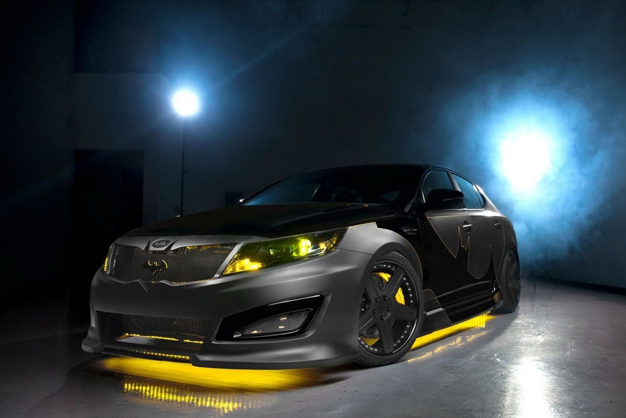 Preview: 2013 Kia Batman Optima  The Batman-themed Optima is the first of a series of eight customized Kia cars that will be released over the next 10 months, with each model representing a character from DC's Justice League. Kia worked together with DC Entertainment and RIDES magazine to design and manufacture Batman's Optima that receives a matte- and piano-black paint scheme with yellow accents and LED lights along with a lowered suspension, a ground effects kit, Ksport performance brakes, custom-designed 20-inch black wheels and a performance exhaust system. Other exterior details worth mentioning is the custom front grille shaped like a batwing and the bat signal etched into the HID headlights. The Optima's interior is upgraded with special seating surfaces in black leather and suede with bold yellow accent stitching, while there's also a Bat suit and cowl awaiting the driver in the trunk.  (vía Carscoop)