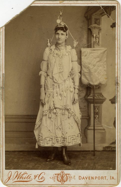 "ca. 1870-1900's, [unusual carte de visite advertising portrait of girl with spoons and bells hanging from her dress, small urns perched on her shoulders, a pedestal with statue and clock seated on her head, etc. A banner by her side reads ""Durfee"" or Durpee""],  J. White & Co. via Jeffrey Kraus, Antique Photographics"