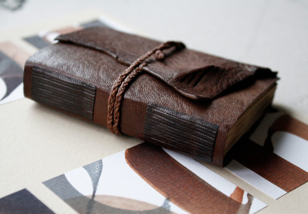 Here's a pocket-sized goatskin journal that I made recently. It features burnt edges and two pared and tooled leather onlays on the back. The cord is hand braided of waxed linen thread. I was first going to make this a bit more intricate but decided to leave it quite blank because it started to look so nice that way. I intend to make something along these lines for sale, too, in the next few months.  Also, hello to all new followers - If you have any comments or questions you can always send them in using my askbox that can be found on top of the page. Thanks for checking my work out!