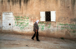 "fotojournalismus:  Palestinian survivor of the 1953 massacre perpetrated by Ariel Sharon walks by a graffiti saying ""Sharon and Barak murders of innocent women and children"". West Bank, Qibya, 2001.  [Credit : Thomas Dworzak]"