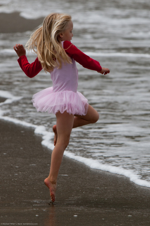 SFW Beauty: Cute Little Girl in Pink Dances on Beach during...