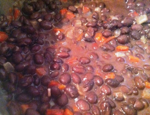 Simple Black Beans (Caraotas Negras)  Original recipe from Cooking Light  Everyone should eat more beans. They're a good source of protein, they're inexpensive, and they're easy to prepare. These beans can be served with breakfast, lunch, dinner, or as a snack, plus they reheat splendidly.  Ingredients  1 1/2 tablespoons canola oil 1 cup chopped onion 1 red bell pepper, chopped 1/2 teaspoon sugar 2 cloves garlic, minced 1/4 teaspoon freshly ground black pepper 1/4 teaspoon ground cumin 1 cup water 2 (15-ounce) cans black beans, undrained 1 teaspoon red wine vinegar Directions   1. Heat oil in a large pot over medium heat. Add onion and bell pepper to pan; cook 5 minutes or until tender, stirring occasionally.    2. Stir in sugar, garlic, black pepper, and cumin; cook 1 minute, stirring constantly. Stir in 1 cup water and beans; bring to a boil.   3. Partially cover, reduce heat, and simmer 30 minutes or until slightly thick, stirring frequently. Remove from heat, and stir in vinegar.  Servings: 4  ♫ Music Pairing: Azealia Banks – Esta Noche  OBSESSED  Website