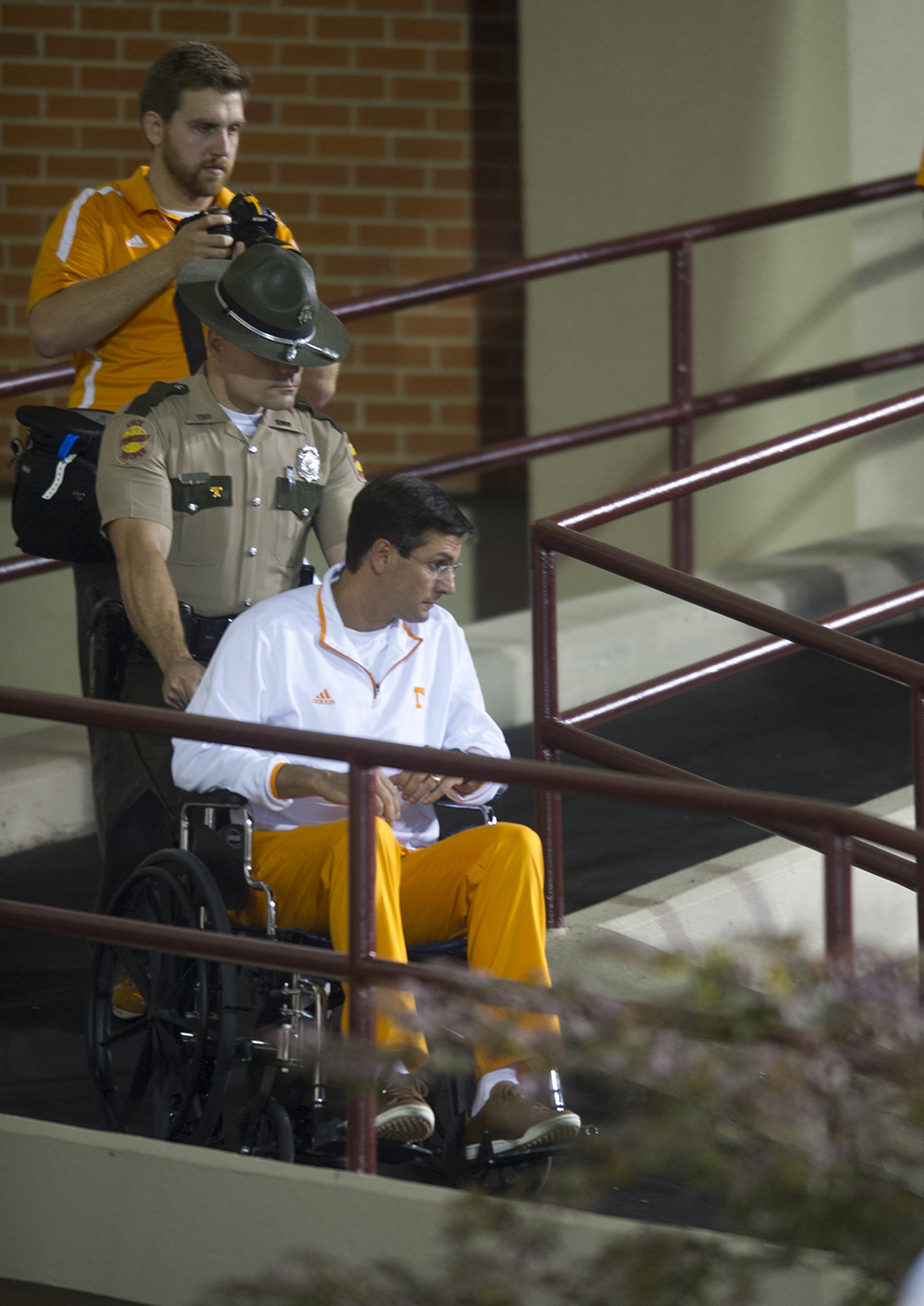 This is not my favorite photo that I shot from the Vols' game at Mississippi State last week, but it has become sports blog fodder since the game. At least three sports blogs I have seen today used this image with their posts. None of them gave proper credit and certainly did not have permission to use this copyrighted photo. Two of the blogs stated that this was taken after the game, which is incorrect.  The photo caption under this photo on www.govolsxtra.com clearly states that it was taken before the game. I digress. Mississippi State's locker rooms are situated a level above the playing field. Players and coaches descend the ramp on foot, or in a wheelchair in this case, before taking the field. Coach Dooley was escorted by this Tennessee Highway Patrol trooper as UT Athletics Department photographer Donald Page, background, photographed the scene. Coach Dooley underwent hip surgery earlier in the week and coached the game from the skybox.  Usually we try to capture the coach on the field, but in this case he was so far away in the skybox that it was nearly impossible to get a photo of him. Moments like this one before the game had to suffice as our only art of Coach Dooley from the game.