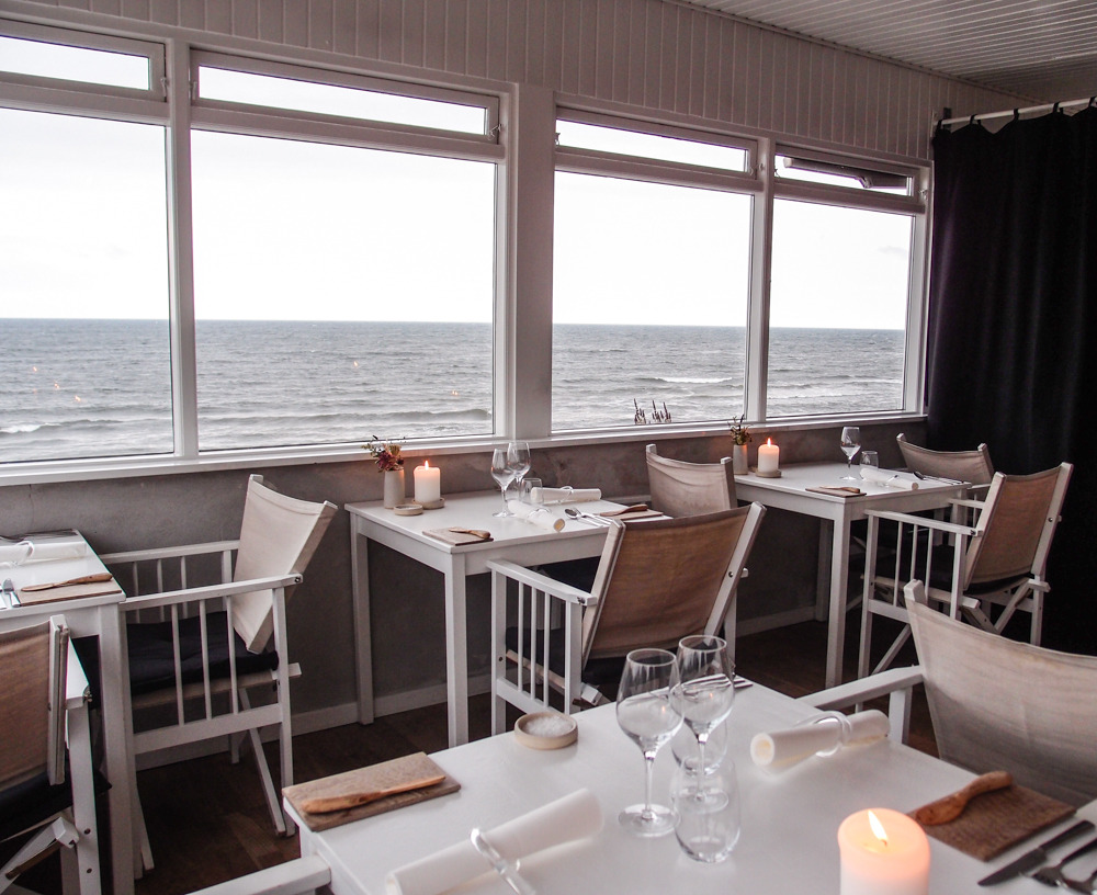 Simple, elegant design in the Bornholm restaurant, Kadeau, on the sea. White, gray, tan, all light neutrals with touches of charcoal send a message of serenity. Light touches of texture and smooth surfaces add interest.