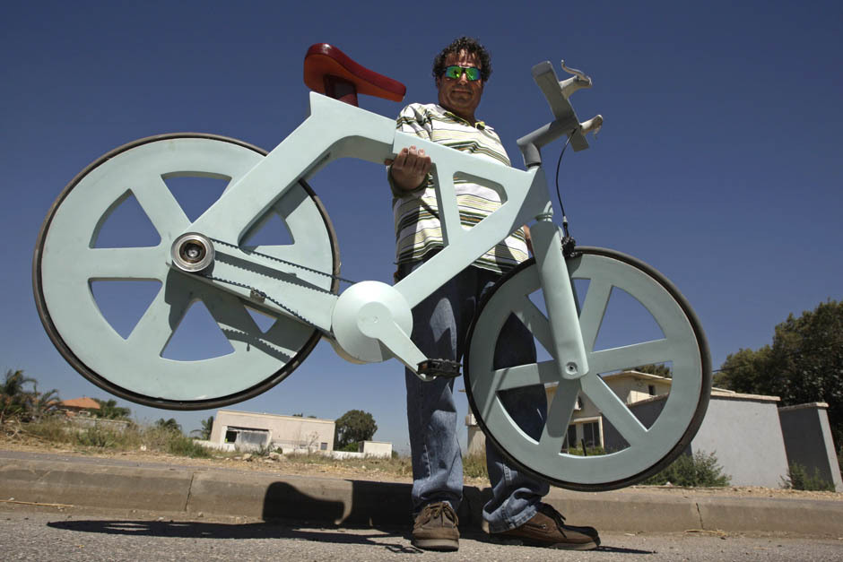 "Israeli inventor creates cardboard bicycle that can 'change the world' A bicycle made almost entirely of cardboard has the potential to change transportation habits from the world's most congested cities to the poorest reaches of Africa, its Israeli inventor says.Izhar Gafni, 50, is an expert in designing automated mass-production lines. He is an amateur cycling enthusiast who for years toyed with an idea of making a bicycle from cardboard.""Making a cardboard box is easy and it can be very strong and durable, but to make a bicycle was extremely difficult and I had to find the right way to fold the cardboard in several different directions. It took a year and a half, with lots of testing and failure until I got it right,"" he said. (REUTERS/Baz Ratner)"