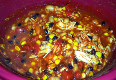 Taco Chicken Chili! Super easy crockpot recipe and it's only 200 calories per serving! Serves 8.  1 can black beans 1 can kidney beans (I used white kidney beans) 1 can corn  28 ounce can diced tomatoes  16 ounce can tomato sauce 1 packet taco seasoning 3 boneless, skinless chicken breasts   Mix all ingredients together in the crockpot and lay the chicken breasts on top. Cook on high for 6 hours. 30 minutes before it's finished, take the chicken out to shred it and mix it back in to continue cooking.  I crumbled multigrain tortilla chips on top to serve!  Enjoy =)