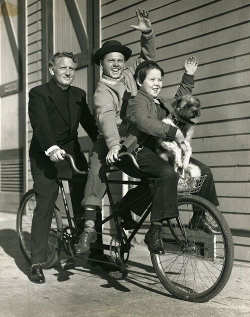 Spencer Tracy, Mickey Rooney, Bobs Wetson and Bohunk ride a tandem — on their way to download a FREE Hollywood Rides a Bike iPad app right here!