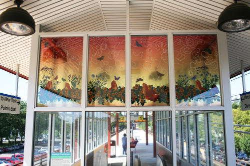 At the Seaford Station on the Long Island Rail Road, artist Carson Fox created Blue Sky Pursuit, consisting of 14 laminated and tempered glass windows. These windows extend the sky creating a bright blue fantasy, filled with butterflies and birds, their flights traced with dots of clear glass that meander, overlap and reveal paths of movement, speaking to migration and the act of travel. The dots also transform the sunlight creating a prismatic effect that enlivens the landscape. Fox used bird and butterfly images inspired from Victorian era engravings, an aesthetic where natural life is a lush and swarming profusion.