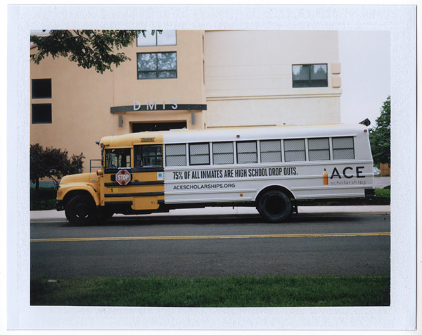 "Denver School Bus Painted as Prison Bus. After making this picture, the school director and his 13-year-old son walked over and asked me what I was doing. My immediate thought was, ""uh oh, here we go…"" They were actually really nice and eager to discuss their thoughts on the prison themed graphics. Both the school director and his son said they hated the negative message of the design. The young boy said he always tries to sit at the front of the bus because he is embarrassed to sit in the prison section. I asked the director why the school agreed to have the prison graphics painted on their school bus. He said they had no choice; it was the decision of ""Ace Scholarships"", and they rely on ""Ace Scholarships"" grant money to keep the school open. ""Polaroids of America"" project. © Jason Paul Roberts, 2012."