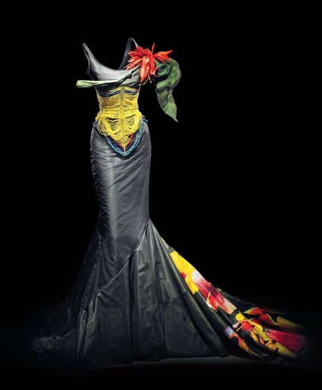John Galliano for Dior Haute Couture, Spring/Summer 1997. Kitu S-line gown in black silk taffeta with fishtail train. Inspired by the corsets worn by warriors of the Dinka tribe in East Africa and the hourglass silhouette of Belle Epoque, this dress features a Masai-style beaded corset and choker, as well as painted tropical flowers in organza.
