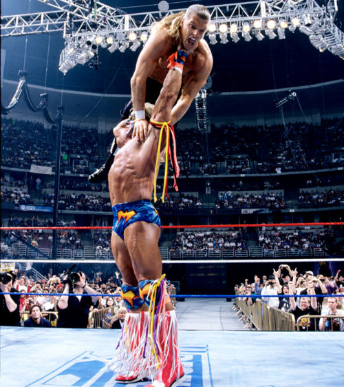 Ultimate Warrior Calmly Holds Up a Terrified Hunter Hearst Helmsley - WWF WrestleMania XII 3/31/1996 A fantastic shot of the ninety-second squash match that was Triple H's Wrestlemania debut. I've looked all over the Internet for a specific quote that I vaguely recall from Hunter about the Warrior, something about how he'd love to set the Warrior's dried-out feathered mullet ablaze for this match, but I cannot find it. I can only find stories about Trips cutting his hair and a link back to this website showcasing Hunter's changed attitude about the Warrior (with a photo from this same match).